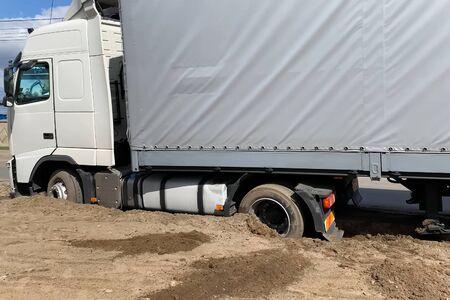 Un camion coincé dans le sable au bord de la route.