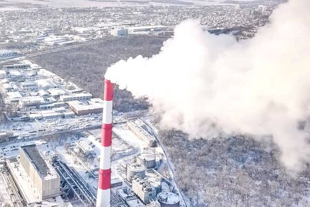 smoking chimney of a thermal power plant on the background of a winter city.