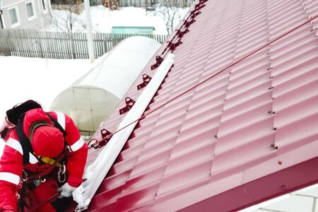 Worker does the installation of the roof of the house. Installation of metal tiles, snow retainers and other elements of the roof.