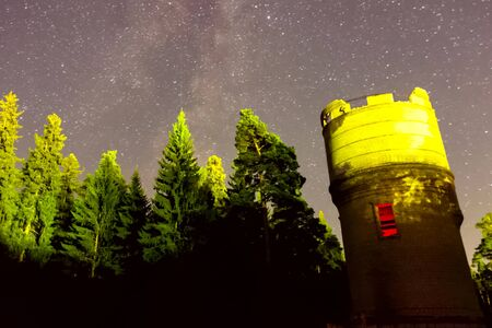 Timelapse Starry sky background video stars in the night sky and the Milky Way. Starry sky over the forest and the water tower.
