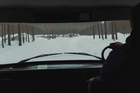 View from the interior of the car into the windshield, winter road through the forest in an SUV.
