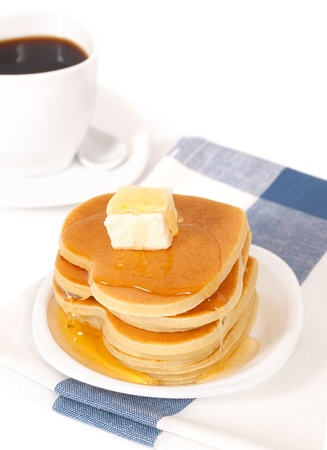 A stack of pancakes with maple syrup and butter. photo