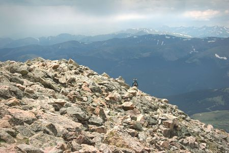 Mountain Summit Woman Hiking Summer Rain Storm. Colorado Summer Mountain Backcountry Scene. Great for themes of nature, summer, mountains, outdoor recreation, travel destinations, background scenics.