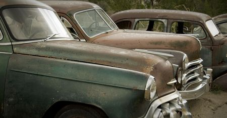 obsolescence: Old rusted cars in the rain at the junkyard looking sad. Good for themes of transportation, retirement, change, aging, retro, nostalgia, memories, family, friendship, humor.