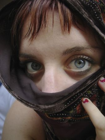 Young woman with scarf around her face reminiscent of the famous national Geographic photo. Close portrait of eyes and veil. Great for themes of relationships, travel, contemplation, romance, trust, youth, religion.