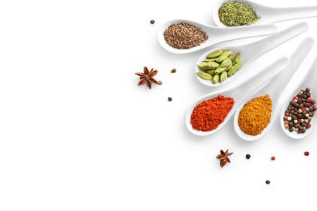 Top view of various spices in spoons isolated on white background. Copy space.