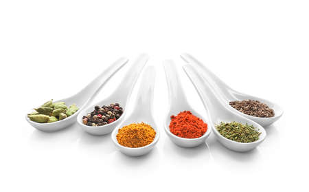 Various spices in spoons isolated on white background.