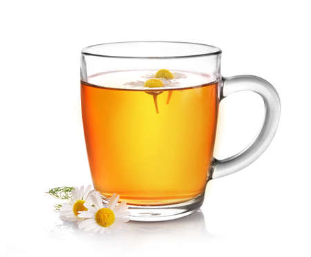 Chamomile herbal tea in glass cup with flower buds isolated on white background. Stockfoto