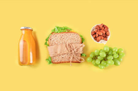 Healthy school lunch on yellow background. Top view.