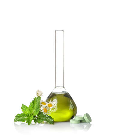 Laboratory flask with natural ingredients and herbal pills isolated on white background. Herbal medicine concept.