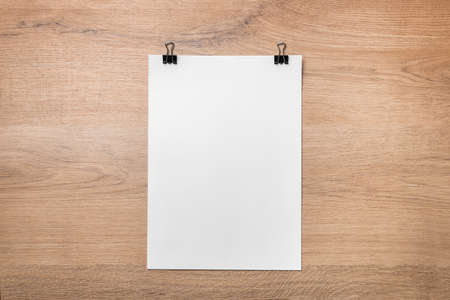 Blank sheet with binder clips on wooden background. Top view. Copy space.