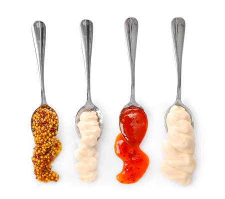 Set of sauces spilling from spoons isolated on white background. Top view.