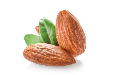 Few almond nuts with leaves isolated on white background.