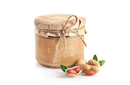 Crunchy peanut butter in glass jar isolated on white background.