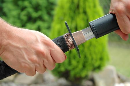 Drawing the sword Katana. Detail of the sword handle.