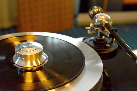 Audiophile turntable with vinyl record. Focus on turntables shiny platter.