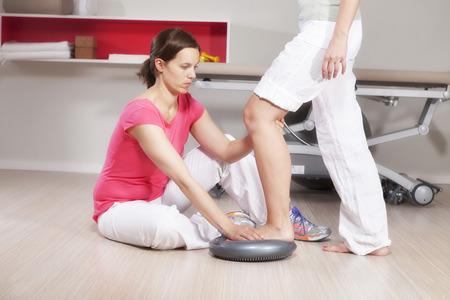 Female osteopath training with patient, exercising balance, Munich, Bavaria, Germany