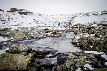 Man speed hiking in snowcapped landscape, river in foreground, Norway, Europe