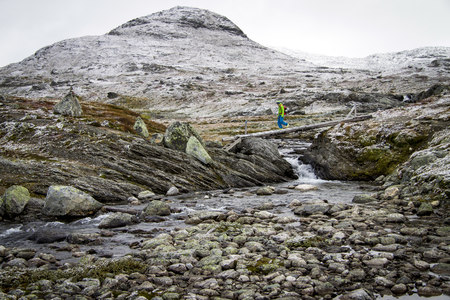conquering adversity: Man speed hiking across mountain stream, Norway, Europe LANG_EVOIMAGES