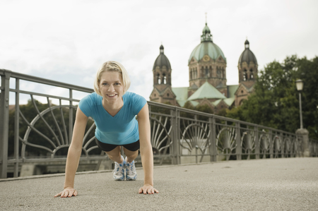 Young woman doing push-ups on bridge, Munich, Bavaria, Germany