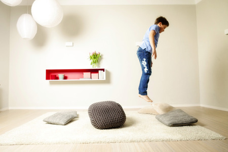Boy jumping across cushions, having fun, Munich, Bavaria, Germany LANG_EVOIMAGES