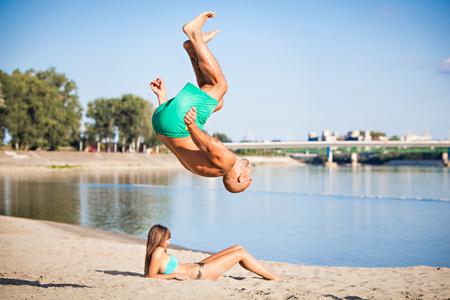 Young man somersaulting on the beach, Drava river, Osijek, Croatia LANG_EVOIMAGES