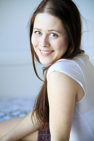 Woman with brown hair sits on bed smiling, Copenhagen, Denmark LANG_EVOIMAGES