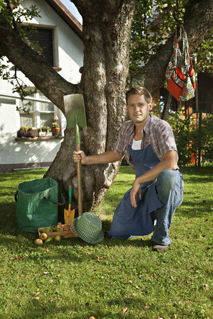 Mid adult man poses next to apple tree in garden, Munich, Bavaria, Germany