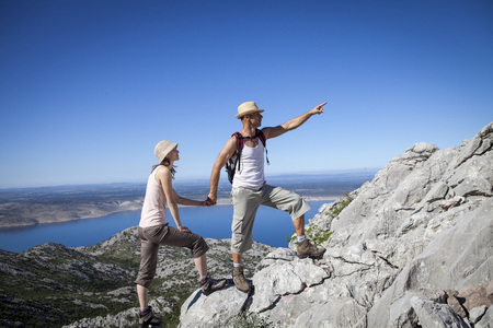Croatia, Paklenica, Couple climbing uphill against blue sky