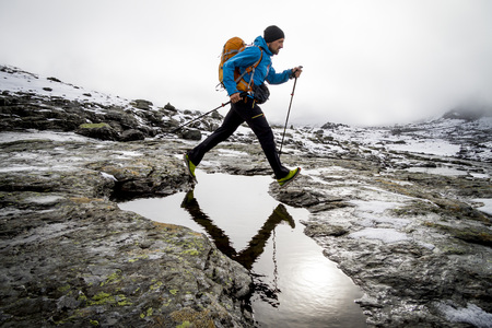 conquering adversity: Hiker crossing mountain stream, Norway, Europe LANG_EVOIMAGES