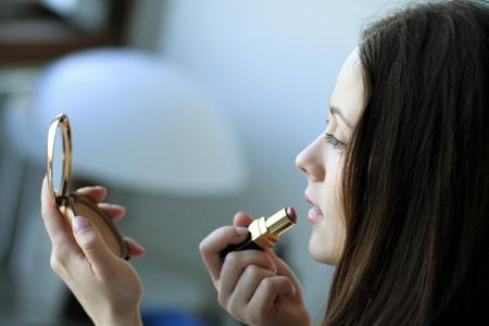 in vain: Woman putting on lipstick, looking into hand mirror, Copenhagen, Denmark LANG_EVOIMAGES
