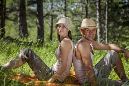Croatia, Paklenica, Young couple relaxes back to back in the grass