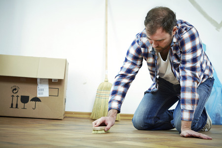 moving box: Man scrubbing the parquet floor, Munich, Bavaria, Germany LANG_EVOIMAGES