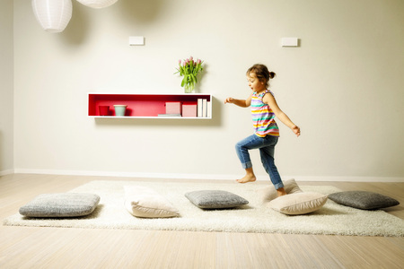 Girl in living room walking across cushions, Munich, Bavaria, Germany LANG_EVOIMAGES
