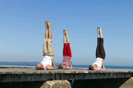 body consciousness: People practising yoga on boardwalk, doing shoulder stand
