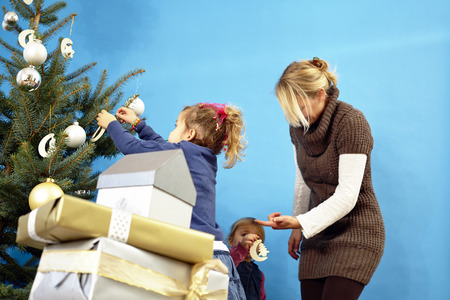 Mother and two girls decorating Christmas tree, Munich, Bavaria, Germany LANG_EVOIMAGES