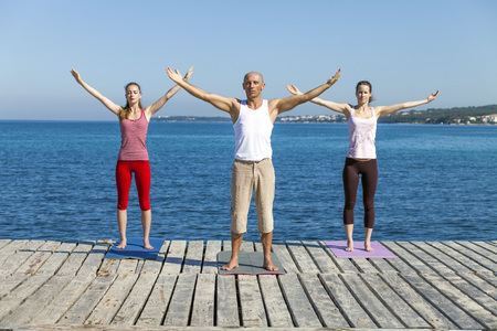 body consciousness: People practising yoga on a boardwalk, arms outstretched LANG_EVOIMAGES