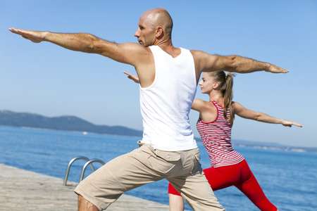 body consciousness: People practising yoga on a boardwalk, warrior pose