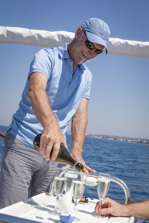 one mature man only: Man on sailboat pouring prosecco into glasses, Adriatic Sea, Croatia LANG_EVOIMAGES