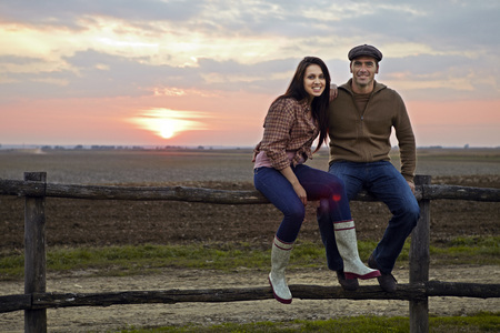 Young Couple Sitting On Wooden Fence, Baranja, Croatia, Europe LANG_EVOIMAGES