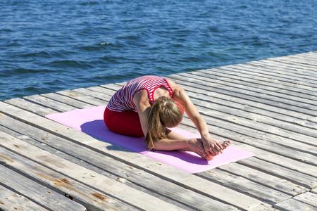 janu: Woman practising yoga on a boardwalk, bending forward