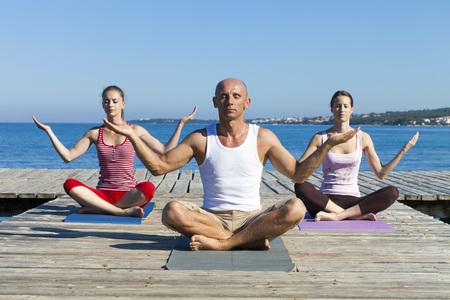 body consciousness: People practising yoga on boardwalk, lotus pose