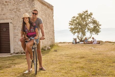 mujer mirando el horizonte: Croatia, Dalmatia, Young couple at the seaside, riding a bike LANG_EVOIMAGES