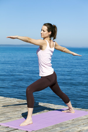 body consciousness: Woman practising yoga on a boardwalk, warrior pose LANG_EVOIMAGES