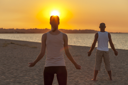 body consciousness: People practising yoga on beach, doing sun salutation LANG_EVOIMAGES