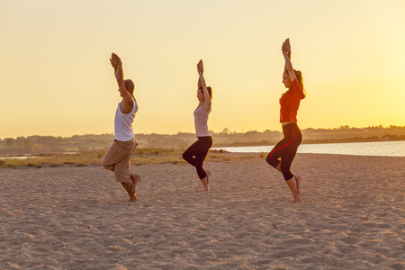 body consciousness: People practising yoga on beach, eagle pose LANG_EVOIMAGES