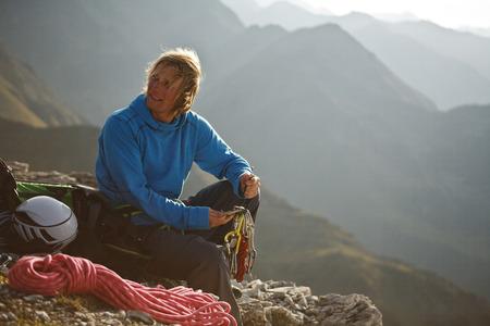 Alpinist sitting in mountains, preparing a climb, Stubai, Kalkkoegel, Austria