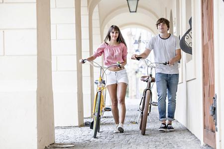 Young couple pushing bicycles, Osijek, Croatia