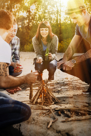 riverbank: Group of friends lighting campfire on a riverbank, Osijek, Croatia