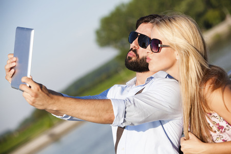 Young couple taking a portrait with digital tablet LANG_EVOIMAGES